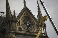 Technicians work in a crane next to the Notre Dame cathedral in Paris, Monday, April 22, 2019. n the wake of the fire last week that gutted Notre Dame, questions are being raised about the state of thousands of other cathedrals, palaces and village spires that have turned France — as well as Italy, Britain and Spain — into open air museums of Western civilization. (AP Photo/Francisco Seco)