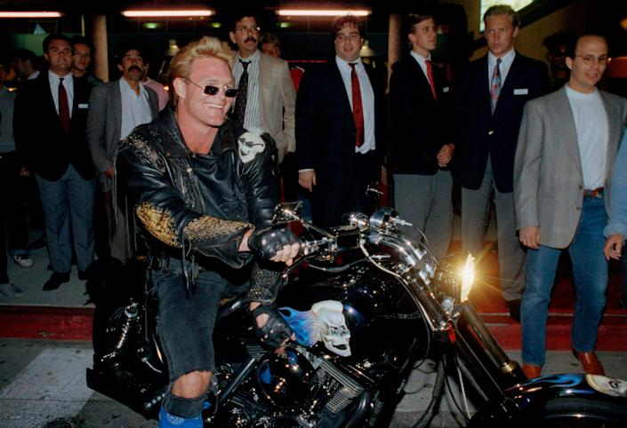 """Brian Bosworth leaves the premiere of his movie, """"Stone Cold,"""" in 1991. He believes the NCAA should consider an annual trust for football players."""