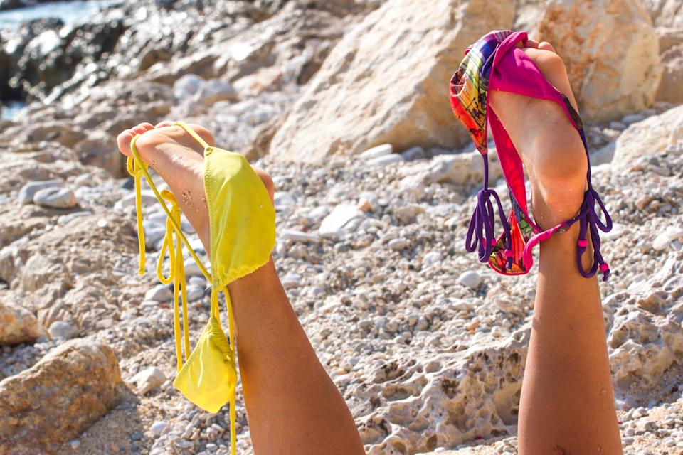 Pair of women's legs raised up. Swimsuit stretched on toes. Holidays without bathing suit, nudism