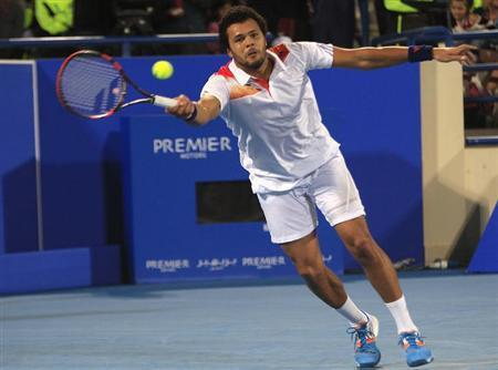 Jo-Wilfried Tsonga of France hits a return to Novak Djokovic of Serbia during their semi-final tennis match at the Mubadala World Tennis Championship in Abu Dhabi December 27, 2013. REUTERS