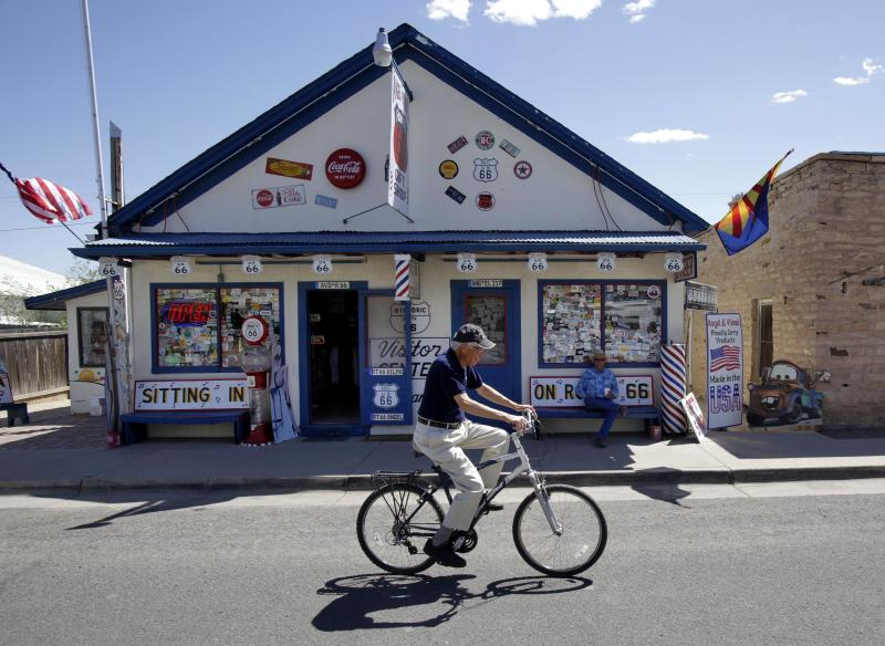 In this Thursday, May 5, 2011 picture, Angel Delgadillo pedals past his souvenir store and barber shop in Seligman, Ariz. Delgadillo, 84, has witnessed the rise and fall of America's most historic byway and gets credit for helping it rise again as Historic Route 66. Telling his story and the road's has become his life's work. (AP Photo/Matt York)