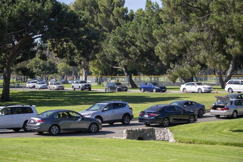 FOUNTAIN VALLEY, CA - OCTOBER 14: Long lines of cars wait as Supervisor Andrew Do and Saddleback Church continue their monthly drive-thru food distributions to needy families that have been impacted by the coronavirus at Mile Square Park on Wednesday, Oct. 14, 2020 in Fountain Valley, CA. 80-100 volunteers loaded 45-55-lb boxes of food for about 1,100 needy families. (Allen J. Schaben / Los Angeles Times)