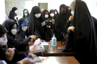 Women register to vote in the presidential election at a polling station in Tehran, Iran, Friday, June 18, 2021. Iran began voting Friday in a presidential election tipped in the favor of a hard-line protege of Supreme Leader Ayatollah Ali Khamenei, fueling public apathy and sparking calls for a boycott in the Islamic Republic. (AP Photo/Ebrahim Noroozi)