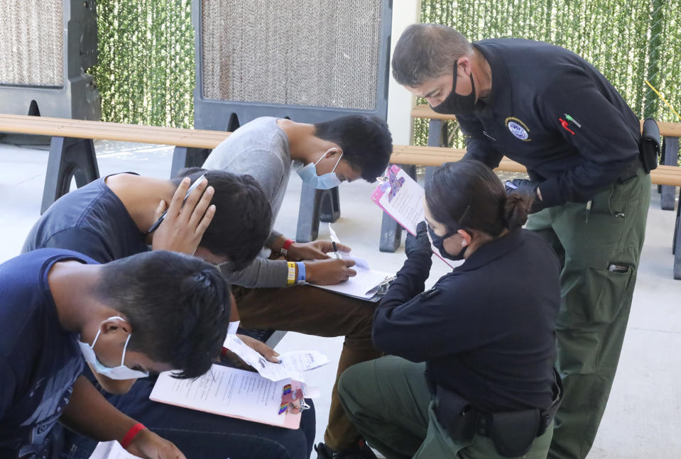 This May 4, 2021, photo provided by The U.S. Border Patrol shows U.S. Border Patrol Processing Coordinators assisting in the processing of underage migrant children at the entrance of the Central Processing Center in El Paso, Texas. The Border Patrol says agents spend about 40% of their time on custody care and administrative tasks that are unrelated to border security, creating a staffing challenge. (U.S. Border Patrol via AP)