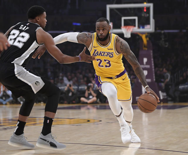 Lakers forward LeBron James drives toward the basket against Spurs forward Rudy Gay during the first half Monday night. (AP)