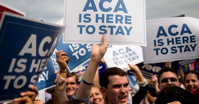 Demonstrators in support of U.S. President Barack Obama's health-care law, the Affordable Care Act (ACA), hold up 'ACA is Here to Stay' signs after the U.S. Supreme Court ruled 6-3 to save Obamacare tax subsidies outside the Supreme Court in Washington, D.C. June 25, 2015.