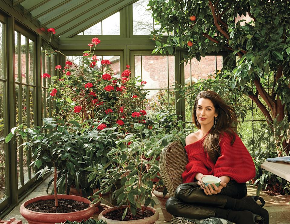 Clooney relaxes at her home in England wearing an Oscar de la Renta sweater and Frame pants. (Photo: Annie Leibovitz/Vogue)