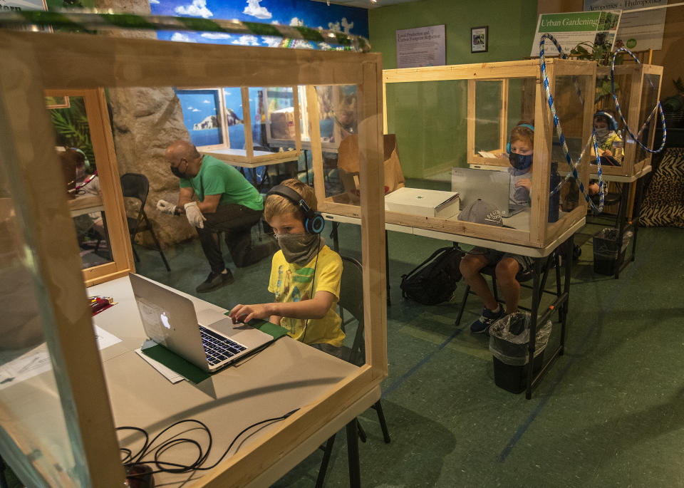 (Left to right) Bennett Krieger, 6, a 1st grader, Antonio Fields, 9, a 4th grader, and Jacob Dartt, 6, a 1st grader, participate in Zoom classes with their respective schools on the first day of class while inside their protective, learning pods at Eco Station in Culver City. (Mel Melcon / Los Angeles Times via Getty Images)