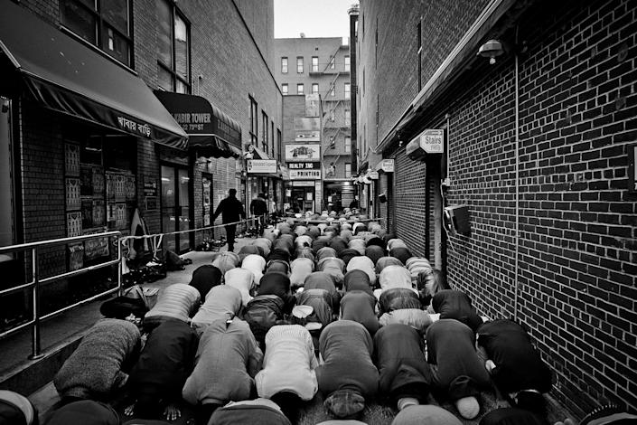 <p>Friday prayer at Darul Hidayah Mosque in Little Bangladesh section of Jackson Heights, Queens, N.Y. Worshipers spilled over to the alley outside the mosque on 73rd Street. (Photo: Yunghi Kim/Contact Press Images) </p>