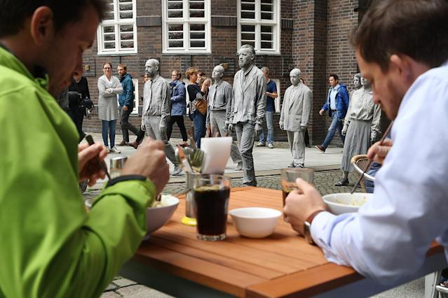 <p>Performance artists covered in clay to look like zombies walk trance-like past an outdoor restaurant in the city center during a preliminary performance on July 5, 2017 in Hamburg, Germany. (Friedemann Vogel/Getty Images) </p>