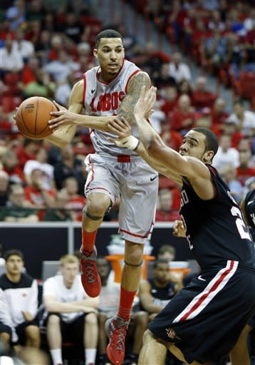 New Mexico's Kendall Williams passes over San Diego State's JJ O'Brien during the first half of a Mountain West Conference tournament NCAA college basketball game on Friday, March 15, 2013, in Las Vegas. (AP Photo/Isaac Brekken)