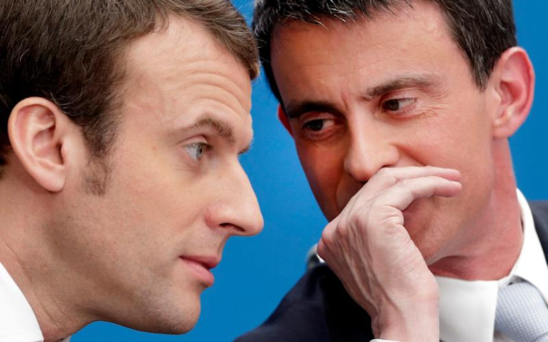 Then French prime minister Manuel Valls, right, speaks with then economy minister Emmanuel Macron - now favourite to become French president - Reuters