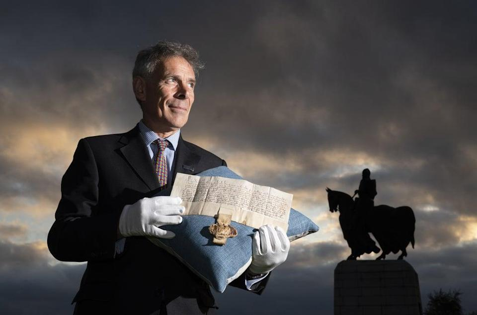 Managing Director of Bonhams Scotland Charles Graham-Campbell holds the Robert the Bruce Letters Patent in his name as King of Scotland alongside the statue of Robert the Bruce at Bannockburn (Jane Barlow/PA) (PA Wire)
