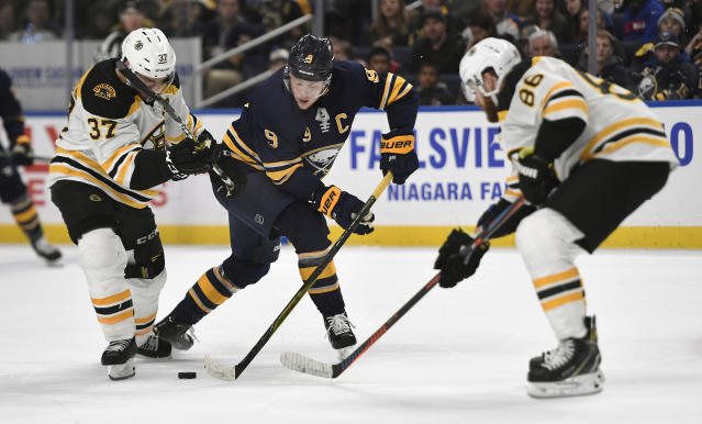 Buffalo Sabres center Jack Eichel, center, battles for the puck against Boston Bruins center Patrice Bergeron (37) and defenseman Kevan Miller (86) during the second period of an NHL hockey game in Buffalo, N.Y., Saturday, Dec. 29, 2018. (AP Photo/Adrian Kraus)