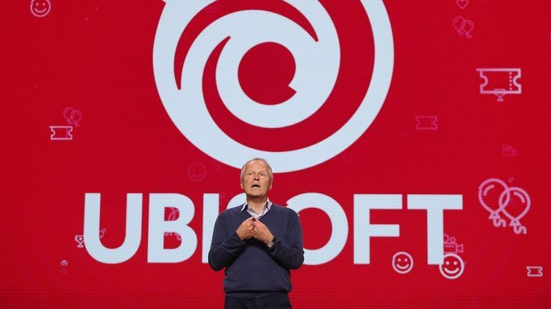 Ubisoft CEO Yves Guillemot standing on a stage at E3 in front of the company's logo.