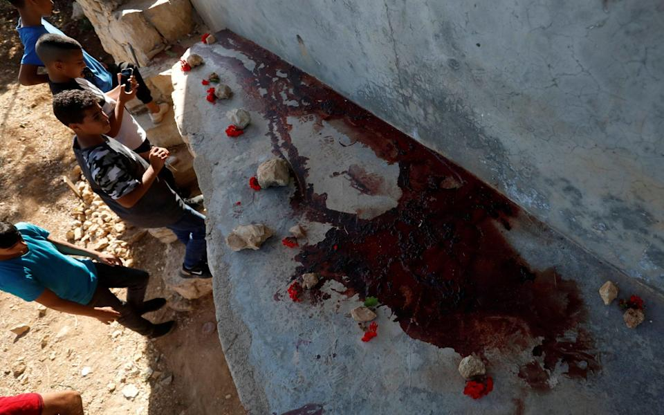 Palestinian kids inspect the scene where Hamas militants were killed by Israeli forces in a gun battle during a raid in Beit Anan - MOHAMAD TOROKMAN /REUTERS