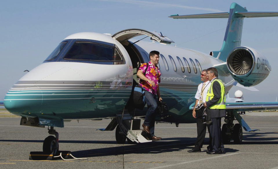 This Aug. 17, 2011 file photo, Jaeger Mah, left, is greeted by Vancouver International Airport CEO Larry Berg, right, and pilot Brent Fishlock as he steps off a Learjet upon arrival at the airport after a short tour in Richmond, B.C. The iconic Learjet, which carried generations of business executives and was made famous in pop songs, is about to fade into aviation history. Canada's Bombardier said Thursday, Feb. 11, 2021 it will end production of the Learjet later this year. (Darryl Dyck/The Canadian Press via AP)