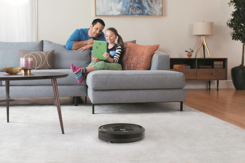A young girl looking at a mobile device while her father looks on, with a robotic vacuum cleaning a carpet in the foreground.