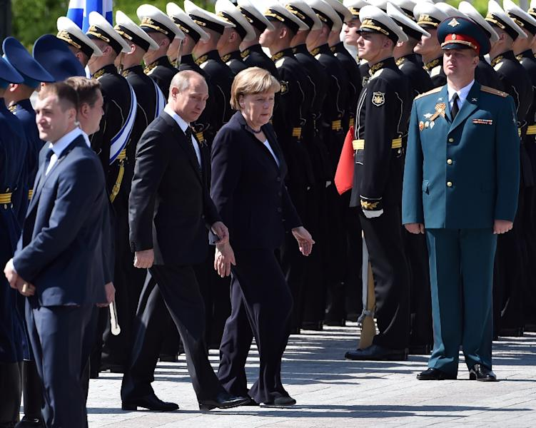 Russian President Vladimir Putin (2ndL) and German Chancellor Angela Merkel (C) attend a wreath-laying ceremony at the Tomb of the Unknown Soldier by the Kremlin Wall in Moscow on May 10, 2015 (AFP Photo/Kirill Kudryavtsev)