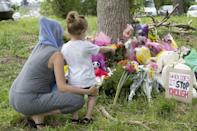 Families pay their respects on June 8, 2021, at a makeshift memorial near the site where a man driving a pick-up truck struck and killed four members of a Muslim family in London, Ontario, Canada