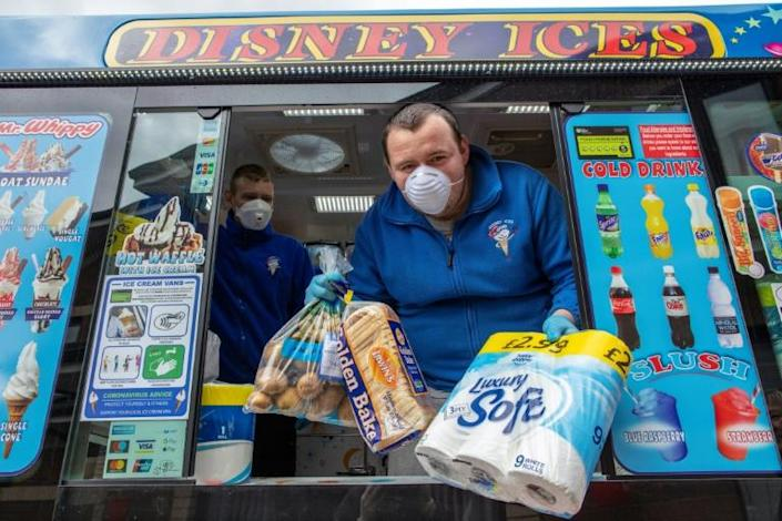 Workers in rubber gloves and face masks sell toilet roll, bread, milk and eggs through the van's hatch (AFP Photo/Paul Faith)