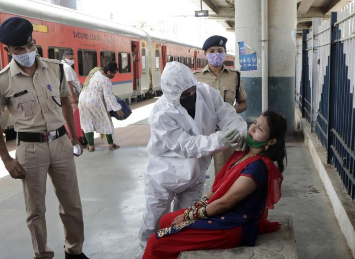 A health worker collects swab sample of traveler to test for COVID-19 at train station in Mumbai, India, Monday, May 24,2020. India crossed another grim milestone Monday of more than 300,000 people lost to the coronavirus as a devastating surge of infections appeared to be easing in big cities but was swamping the poorer countryside. (AP Photo/Rajanish kakade)