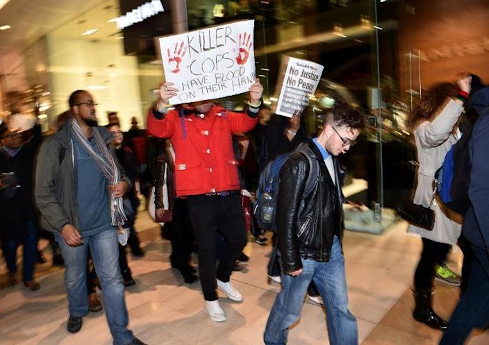 Protesters hold placards as they walk around the Westfield shopping mall in West London on December 10, 2014, in support of protests in the US over the killings of black suspects by white police officers (AFP Photo/Leon Neal)