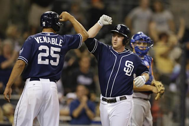 San Diego Padres' Jedd Gyorko, center, bumps elbows with teammate Will Venable, left, after hitting a three-run home run as New York Mets catcher Travis d'Arnaud looks on at right during the eighth inning in a baseball game Saturday, Aug. 17, 2013, in San Diego. (AP Photo/Gregory Bull)