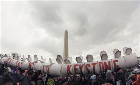 Demonstrators carry a replica of a pipeline during a march against the Keystone XL pipeline in Washington