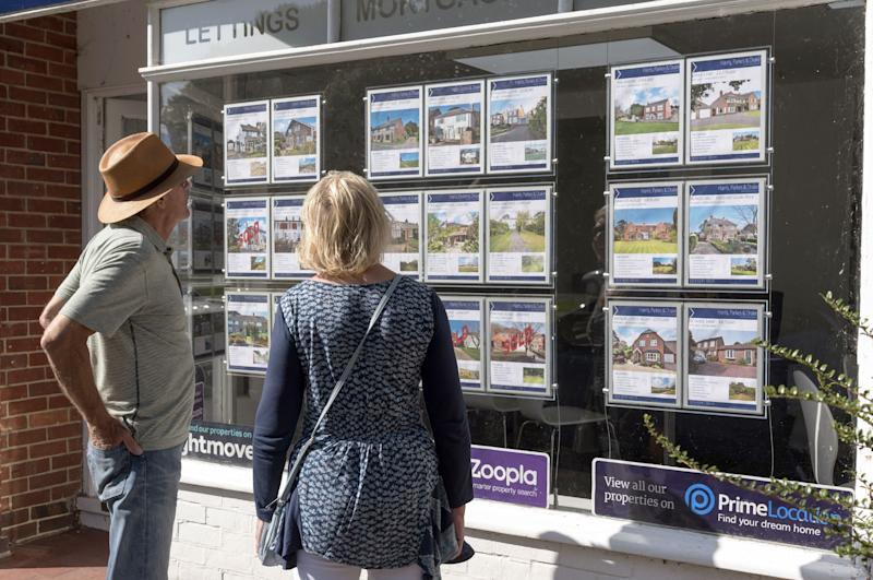 Couple looking at estate agent window