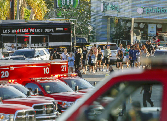 <p>A Los Angeles Police SWAT team escorts a group of people who were held for their safety across businesses surrounding Trader Joe's supermarket, after a gunman had barricaded himself inside a Trader Joe's store in Los Angeles on Saturday. (Photo: Damian Dovarganes/AP) </p>