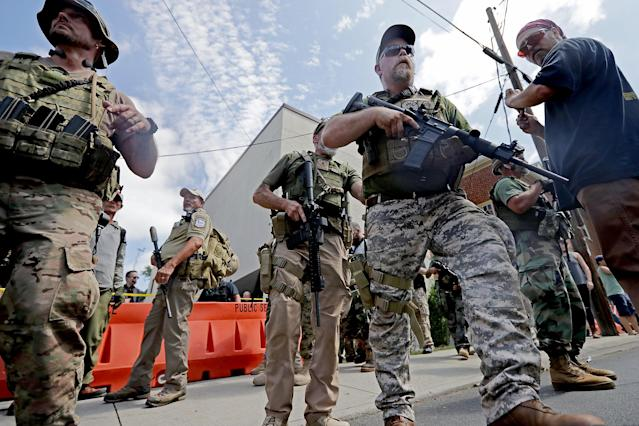"<p>White nationalists, neo-Nazis and members of the ""alt-right"" with body armor and combat weapons evacuate comrades who were pepper sprayed after the ""Unite the Right"" rally was delcared a unlawful gathering by Virginia State Police Aug. 12, 2017 in Charlottesville, Va. (Photo: Chip Somodevilla/Getty Images) </p>"