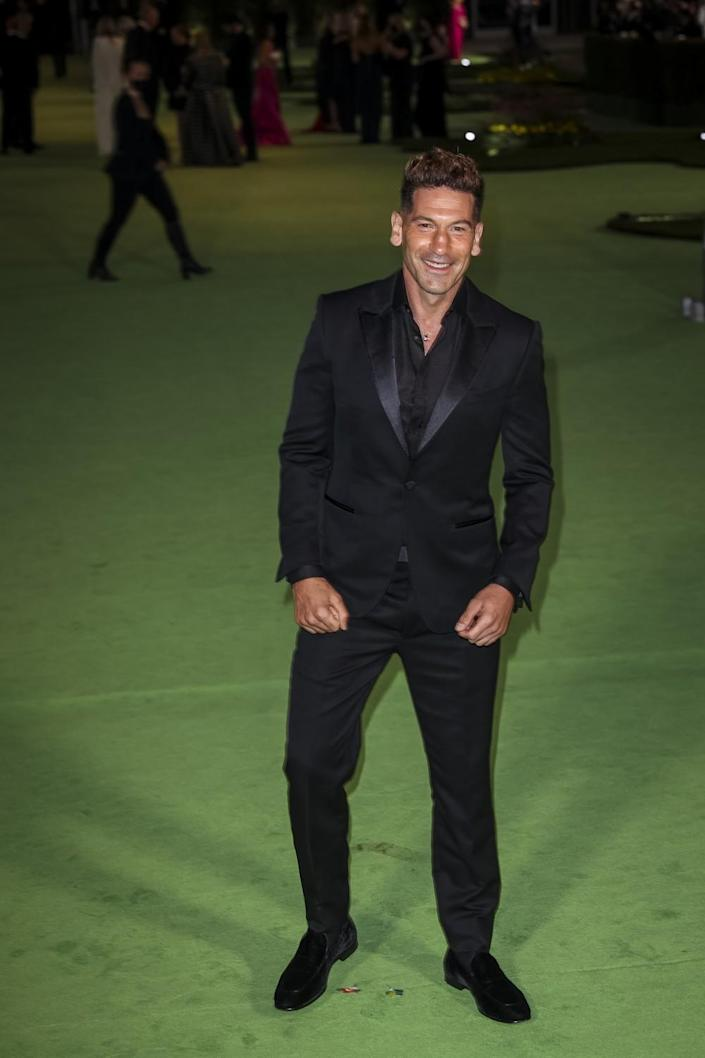 A man in a black suit posing on a green carpet