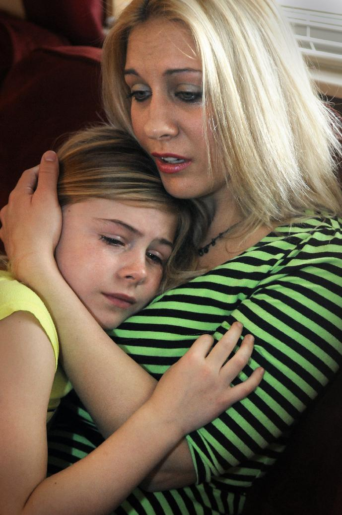 Becky Decker holds her 8-year-old daughter Kelly in their Sartell, Minn., home Saturday, Dec. 1, 2012. Kelly's father, Richmond Police Officer Tom Decker, 31, was killed late Thursday, Nov. 29 in what police say was an ambush near Winner's Bar in Cold Spring. (AP Photo/The St. Cloud Times,Dave Schwarz)  NO SALES
