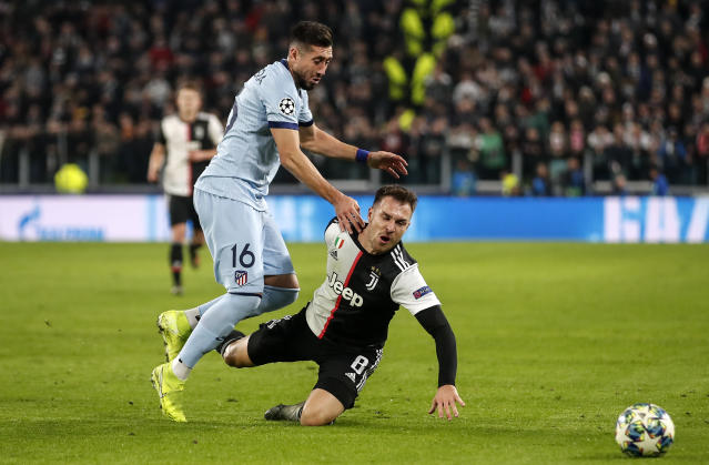Atletico Madrid's Hector Herrera, left, and Juventus' Aaron Ramsey challenge for the ball during the Champions League group D soccer match between Juventus and Atletico Madrid at the Allianz stadium in Turin, Italy, Tuesday, Nov. 26, 2019. (AP Photo/Antonio Calanni)
