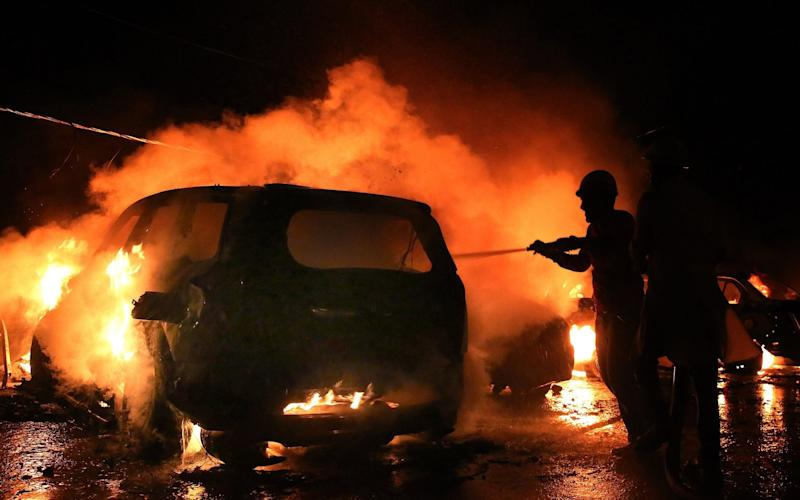 car on fire in India after riot - Credit: Sanjeev Gupta/EPA