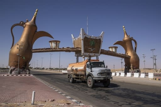 In this Monday, Jan. 13, 2020 photo, a track drives past the entrance gate of Wadi Al Dawasir, Saudi Arabia. Formerly known as the Paris-Dakar Rally, the race was created by Thierry Sabine after he got lost in the Libyan desert in 1977. Until 2008, the rallies raced across Africa, but threats in Mauritania led organizers to cancel that year's event and move it to South America. It has now shifted to Saudi Arabia. The race started on Jan. 5 with 560 drivers and co-drivers, some on motorbikes, others in cars or in trucks. Only 41 are taking part in the Original category. (AP Photo/Bernat Armangue)