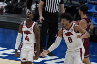 Arkansas' Davonte Davis (4) celebrates with Justin Smith (0) after Davis made a basket as time expired for the first half of a first round game against Colgate at Bankers Life Fieldhouse in the NCAA men's college basketball tournament, Friday, March 19, 2021, in Indianapolis. (AP Photo/Darron Cummings)