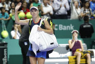 Caroline Wozniacki of Denmark, left, waves after as she leaves competing against Elina Svitolina of the Ukraine after their women's singles match at the WTA tennis finals in Singapore, Thursday, Oct. 25, 2018. (AP Photo/Vincent Thian)