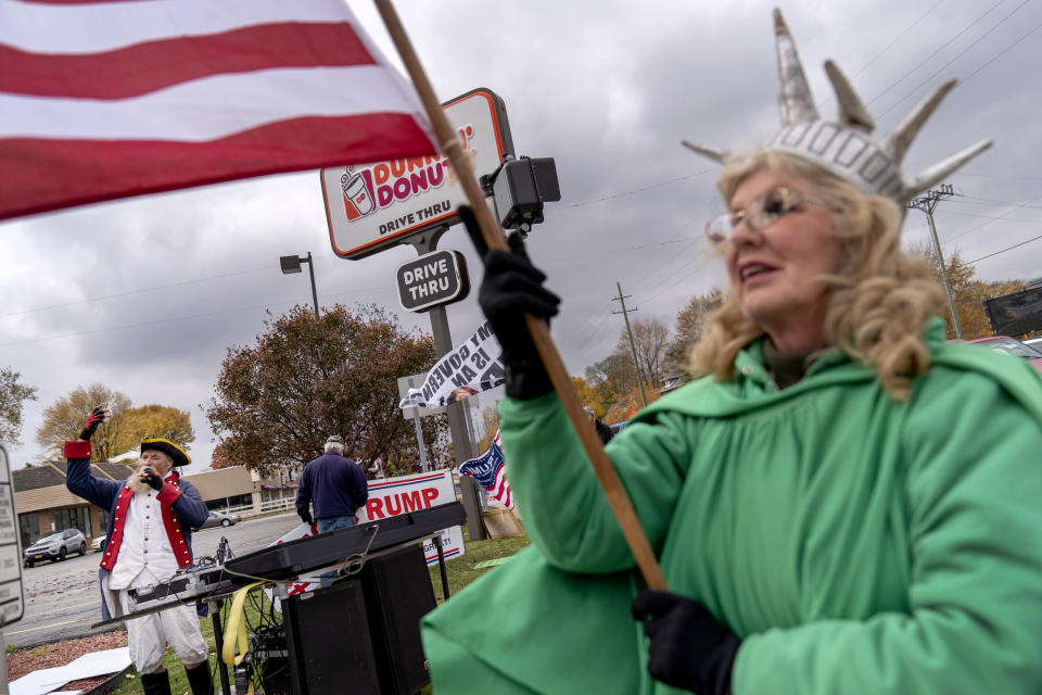 Trump supporters Carol Reed, dressed as the Statue of Liberty, right, and Matthew Woods, dressed as a Continental Army soldier, cheer at an intersection during a rally in Mount Clemens, Mich., Thursday, Oct. 29, 2020. About 7 in 10 voters say they are anxious about the election, according to an AP-NORC poll last month. Only a third are excited. Biden supporters were more likely than Trump voters to be nervous, 72% to 61%. (AP Photo/David Goldman)