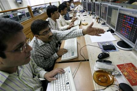 Stock brokers engage in trading at a brokerage firm in Mumbai