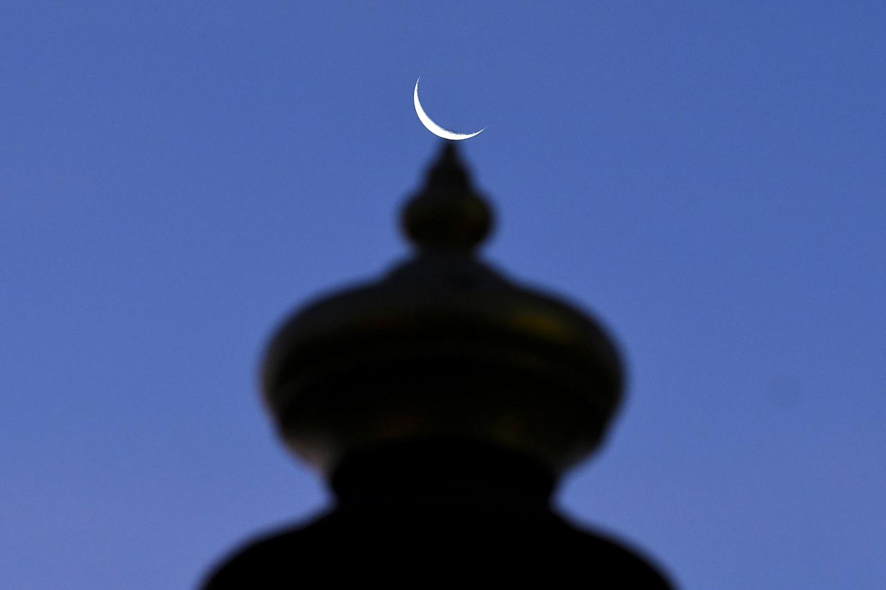 A crescent moon is pictured on top of the Sultan Ismail Petra Arch, a landmark of Kota Bharu in Kelantan, Malaysia April 13, 2018. Picture taken April 13, 2018. REUTERS/Stringer     TPX IMAGES OF THE DAY