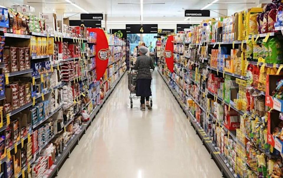 Woman shopping in supermarket aisle. Source: Getty Images