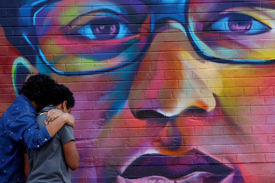 Visitors in Denver pause before a mural of Elijah McClain, before the first anniversary of his death.