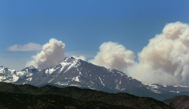 Plumes of smoke from the Big Meadows Fire in Rocky Mountain National Park rise above Longs Peak, as seen from just east of Boulder, Colo., Tuesday June 11, 2013. A National Park crew assessed the fire that has been confirmed on the north end of Big Meadows on the west side of the park. (AP Photo/Brennan Linsley)