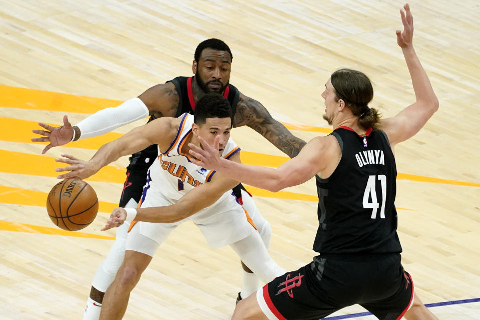Phoenix Suns guard Devin Booker is pressured by Houston Rockets forward Kelly Olynyk (41) and guard Armoni Brooks during the first half of an NBA basketball game, Monday, April 12, 2021, in Phoenix. (AP Photo/Matt York)