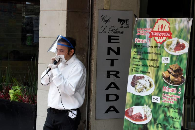 A worker of La Blanca Restaurant uses a microphone to advertise the menu in Mexico City, on July 01, 2020 during the COVID-19 pandemic. - Starting this week Mexico City is allowing the reopening of restaurants, shops, street markets and athletic complexes but with limited capacity and hours. (Photo by Alfredo ESTRELLA / AFP) (Photo by ALFREDO ESTRELLA/AFP via Getty Images)