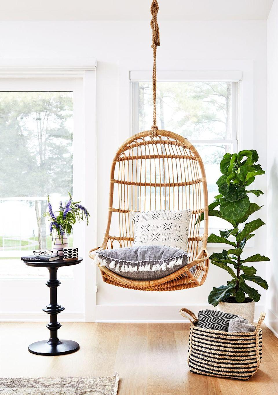 <p>A rattan swing chair adds a playful touch to this bedroom's reading space. </p>