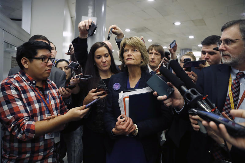 Sen. Lisa Murkowski, surrounded by reporters, leaves a session of the impeachment trial of President Trump. (Julio Cortez/AP)