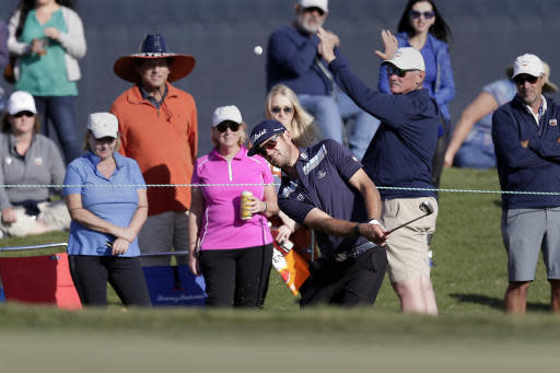 Lanto Griffin chips onto the 18th green as the gallery looks on during the third round of the Houston Open golf tournament Saturday, Oct, 12, 2019, in Houston. (AP Photo/Michael Wyke)